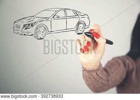 Business Woman Draws A Model Car On A Gray Background
