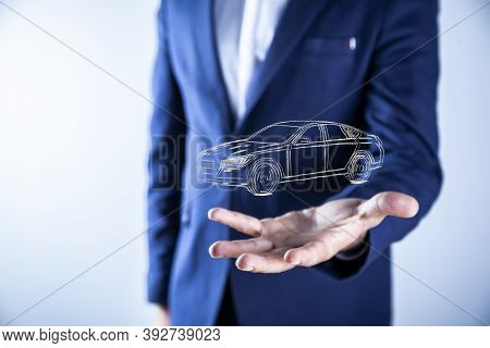 Businessman In Suit Holding Virtual Car On Dark Background