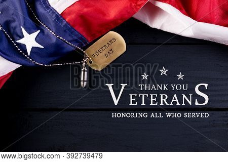 Closeup Of A Dog Tag With The Text Veterans Day Engraved In It With Usa Flag On Black Wooden Backgro