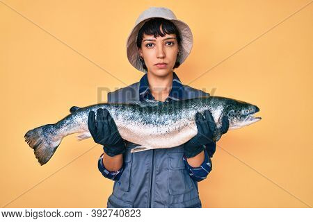 Beautiful brunettte fisher woman showing raw salmon relaxed with serious expression on face. simple and natural looking at the camera.