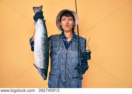 Beautiful brunettte fisher woman holding fishing rod and raw salmon looking at the camera blowing a kiss being lovely and sexy. love expression.