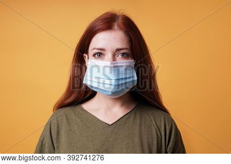 Studio Portrait Of Young Woman Wearing A Medical Face Mask Covering Mouth And Nose - Protection Agai
