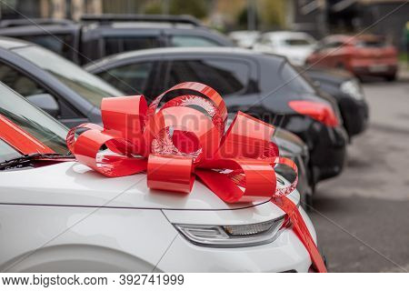 A White Car With A Big, Red Bow On The Hood Is On The Street, An Expensive Gift, A New Car As A Gift