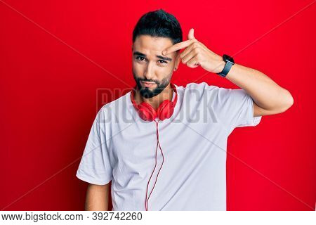 Young man with beard listening to music using headphones pointing unhappy to pimple on forehead, ugly infection of blackhead. acne and skin problem