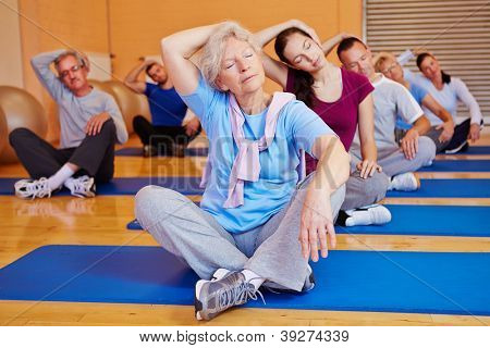 Group doing stretching exercises in back training class in a fitness center