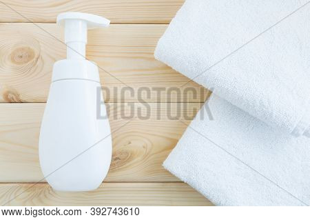 White Bottle With Dispenser And Two White Towels On A Natural Wooden Background. Flat Lay, Top View.