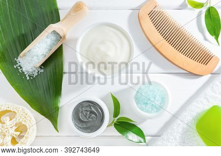 Natural Organic Spa Products, Body Care Accessories And Fresh Green Plants On White Wooden Backgroun