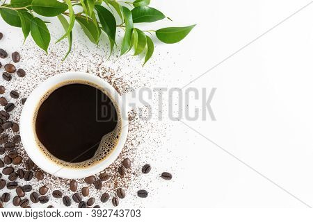 Cup Of Americano Coffee, Coffee Beans And Green Leaves On White Background. Flat Lay, Top View, Copy
