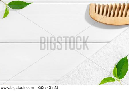 Creative Background For Natural And Spa Cosmetics Concept With Green Plants, Wooden Comb And Towel.