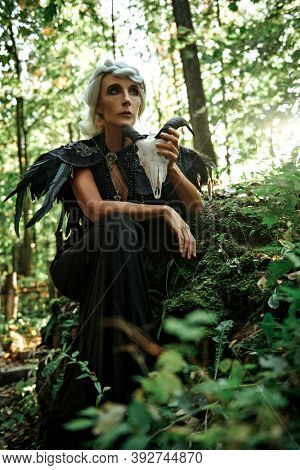 A sad aristocratic  old widow woman with beautiful gray hair and a rich black dress is posing holding skull in her hands in a cemetery. Black Widow. Atmosphere of mysticism. Halloween.