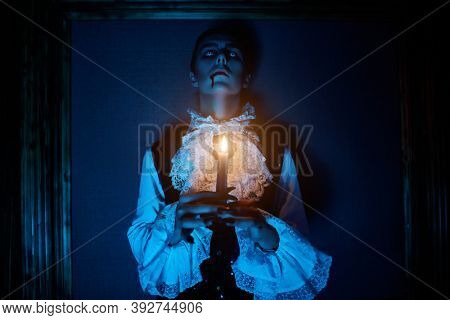 A bloodthirsty vampire aristocrat is looking up holding a candle in his hands. 19th century style. Halloween.
