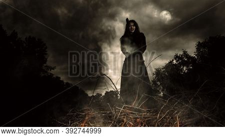 A portrait of an witch tied for incineration. Magic, dark force, spell.