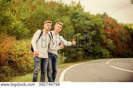 Travellers On Their Way. Friends Hitchhikers Travelling. Hitchhiking Gesture. Begin Great Adventure