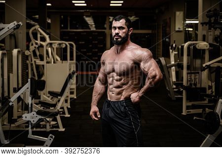 Strong Young Adult Bearded Male With Perfect Sport Muscle Physique In Dark Night Indoors Gym Among W