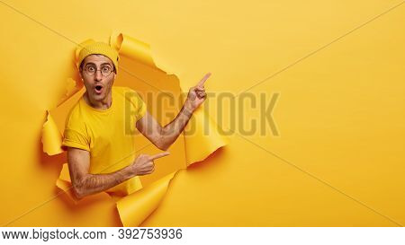 Indoor Shot Of Impressed Delighted Unshaven Man Points Away At Upper Right Corner, Poses Through Tor