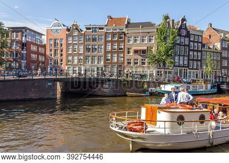 Amsterdam, Netherlands - 3 September, 2012: Tourists Walking By A Canal In Amsterdam. Amsterdam Is T