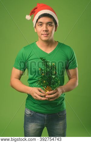 Young Handsome Filipino Man Ready For Christmas Against Green Background