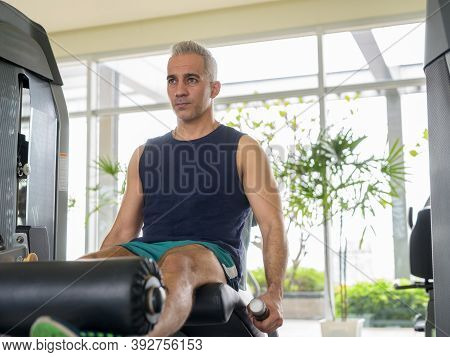 Mature Handsome Persian Man Doing Leg Extension Exercise At The Gym
