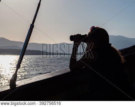Woman looking at the sea through binocular
