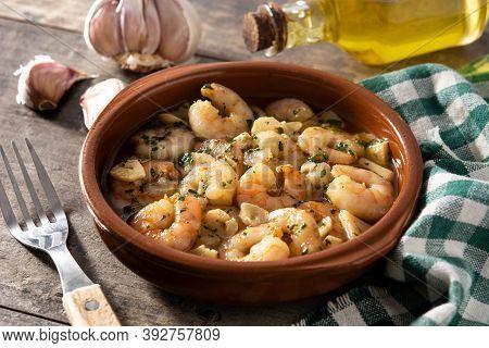 Garlic Prawns In Crockpot On Wooden Table.