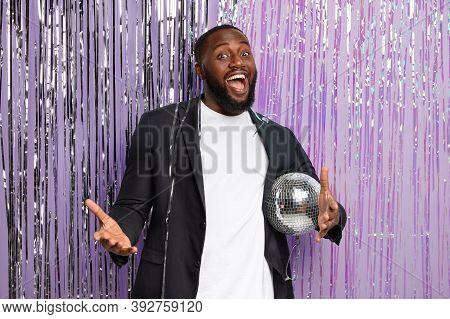 Joyful Dark Skinned Man Enjoys Night Dance Party Music Holds Shining Disco Ball, Dressed In Classy B