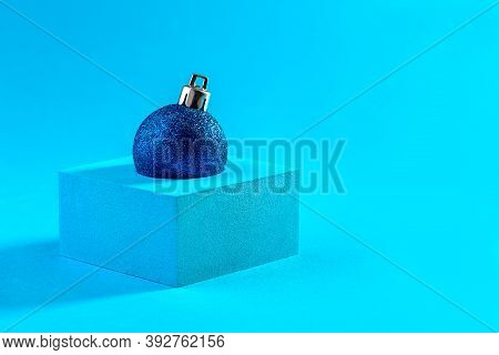 Christmas Blue Glitter Ball On The Podium On A Blue Background With Copy Space. Christmas Minimal Co