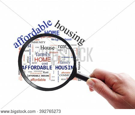 Hand With Magnifying Glass Looking At Affordable Housing Word Cloud In The Shape Of A House, On Whit