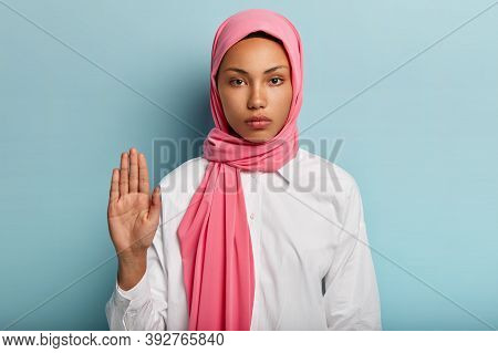 Slow Down And Stop. Serious Dark Skinned Arabic Woman Shows Refusal Gesture, Raises Palm Towards Cam