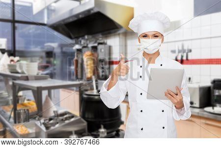 cooking, culinary and health concept - female chef in toque wearing face medical mask for protection from virus disease with tablet pc computer showing thumbs up over kebab shop kitchen background