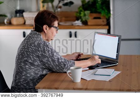 Senior Woman Using Laptop For Websurfing In Her Kitchen. The Concept Of Senior Employment, Social Se