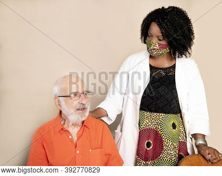 Horizontal Portrait Of An African American Medical Assistant Wearing A Mask And Helping An Ederly Ma