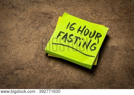 16 hour fasting reminder note on a brown textured bark paper, healthy lifestyle, intermittent fasting, diet and weight loss, time-restricted eating, daily eating window concept