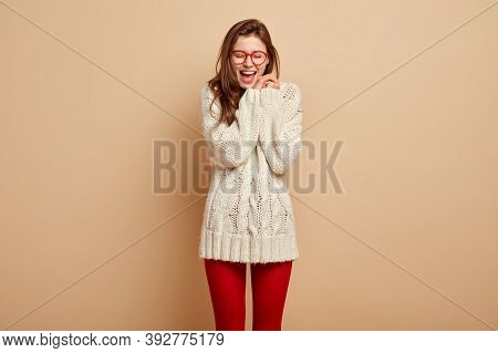 Overjoyed European Woman Laughs Sincerely, Keeps Hands Together Near Face, Keeps Mouth Opened, Pleas