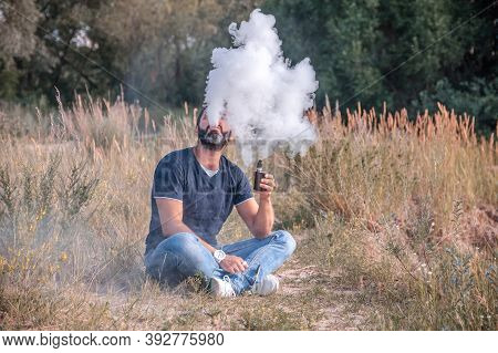 Stylish Bearded Man Vaping An Electronic Cigarette In Nature. The New Technology Cigarette.