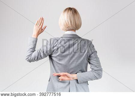 Female Politician Swearing Oath With Fingers Crossed Behind Back On Light Grey Studio Background. Bu