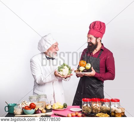 Two Chefs On Kitchen. Kitchen. Cooking. Beared Chef Man. Delicious Food. Male Chef In Uniform. Chef,
