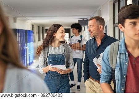 Happy high school student talking to mature man professor in hallway. Senior man teacher in conversation to school girl in campus. Helpful lecturer explaining concept to college student in corridor.