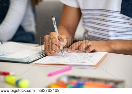 Close up of african student giving exam writing on paper. Closeup of black guy hands marking answers on examination in college. Student hand fiiling out answers with multiple questions on the test.