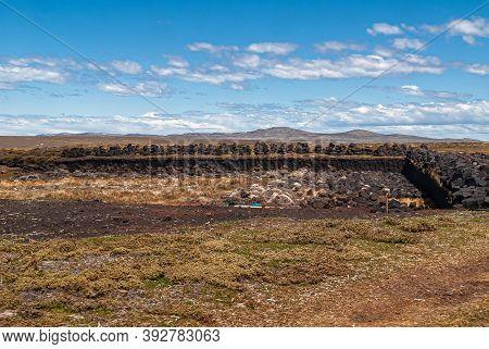 Falkland Islands, Uk - December 15, 2008: Wide Windswept Bare Landscape Of Dry Land With A Peat Harv