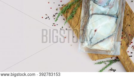 Sous-vide Cooked Technology Concept. Vacuum Fillet Of Fresh Atlantic Snow White Fish On Wooden Board