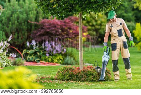 Caucasian Men In His 40s With Modern Electric Cordless Leaf Blower Cleaning His Backyard Garden.