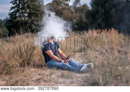 Handsome Vape Man Blows Up A Couple An E-cigarette. Electronic Cigarette As Alternative To Tobacco.