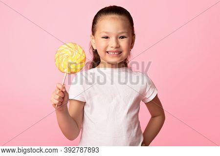 Children And Sugar Addiction. Portrait Of Positive Asian Girl Smiling, Holding Swirl Spiral Lollipop
