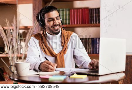 Cheerful Indian Teacher At Laptop Computer Teaching Online Having Remote Class With Distant Student