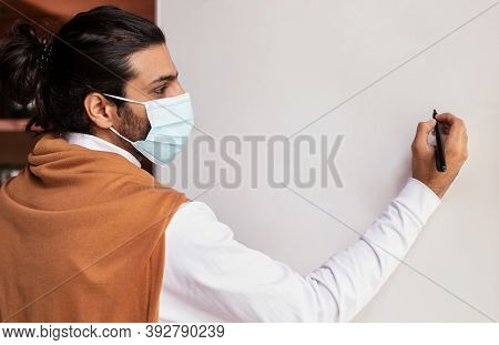 Teacher Man In Face Mask Teaching Writing On Blank White Blackboard Having Class Standing Indoors. S