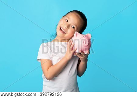 My Savings Concept. Portrait Of Positive Asian Girl Shaking Pink Piggy Bank And Listening Whats Insi