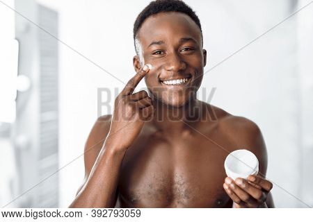 Male Facial Skincare. Cheerful Black Man Applying Cream On Smooth Face Caring For Skin After Shaving