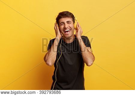 Positive Human Emotions And Fun Concept. Happy Joyous Caucasian Man Keeps Both Hands On Modern Headp