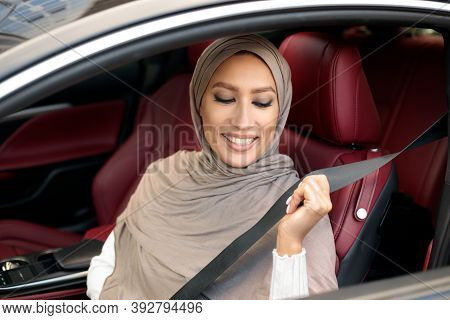Safety First. Smiling Muslim Lady In Hijab Fastening Seatbelt Before Driving In City. Young Woman Si
