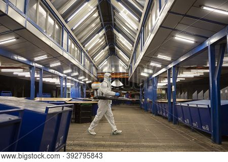 Sofia, Bulgaria - 7 April, 2020: Worker Sprays Disinfectant Outside Of ? Food Market Against The Spr